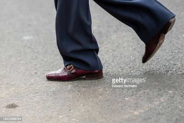 Guest wears navy blue suit pants, a gold ring, burgundy leather crocodile pattern shoes, outside the Fendi fashion show during the Milan Fashion Week...