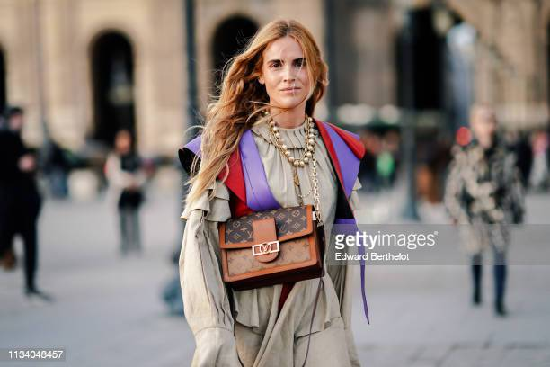 A guest wears necklaces a beige pleated and ruffled top a purple and red leather bolero a Louis Vuitton bag outside Louis Vuitton during Paris...
