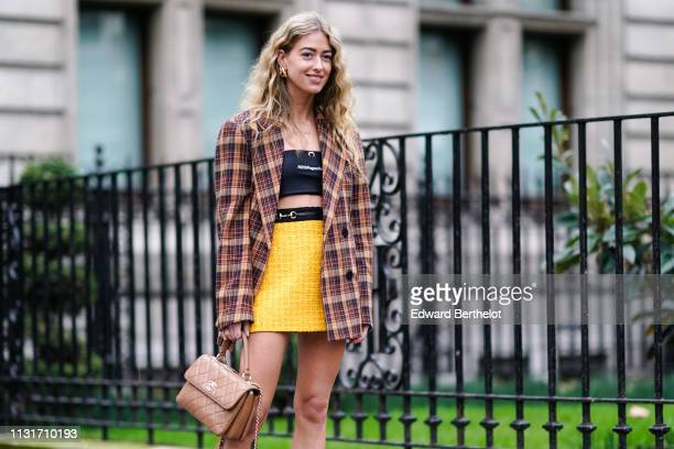 A guest wears necklaces a black H2OFagerholt training bra a yellow miniskirt a camel black and brown tartan jacket a salmoncolor Chanel handbag...