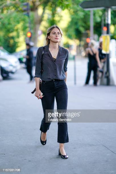 Guest wears necklaces, a black shirt with white tiny polka dots, navy blue denim flare crop pants, shiny black flat shoes, outside AMI, during Paris...