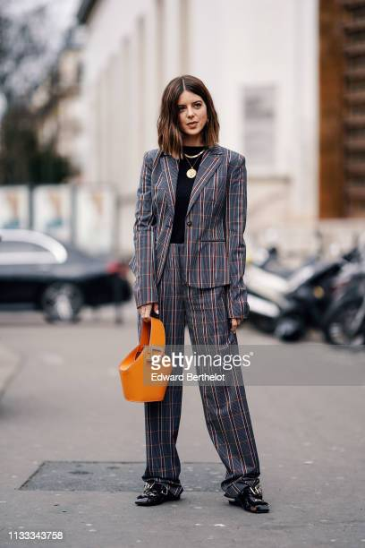 Guest wears necklaces, a black top, a grey and red striped pantsuit with oversize pants, black mules, an orange Danse Lente bucket handbag, outside...