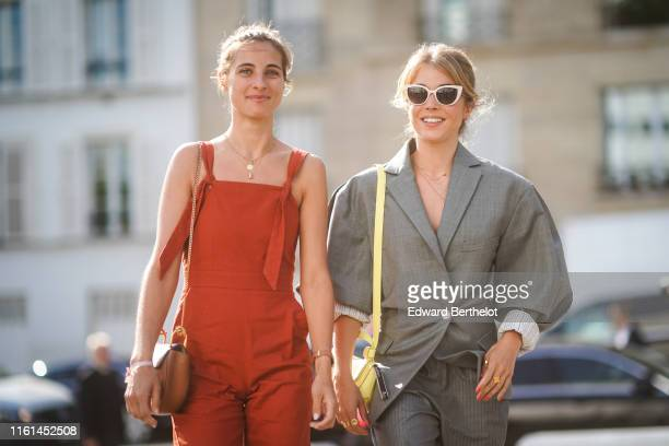 A guest wears necklaces a brown bag a red strappy jumpsuit A guest wears white sunglasses a yellow Acne Studios bag necklaces a grey striped pantsuit...