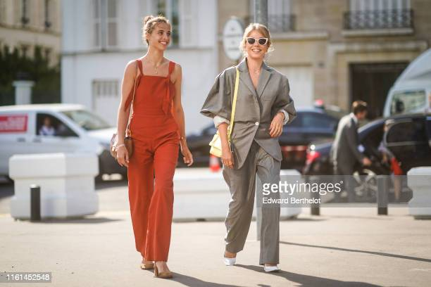 A guest wears necklaces a brown bag a red strappy jumpsuit with flare pants brown slingback pumps A guest wears white sunglasses a yellow Acne...