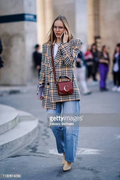 A guest wears necklaces a brown Chloé bag a black and camel checkered jacket a white top baggy jeans beige highheeled pointy boots outside Dries Van...