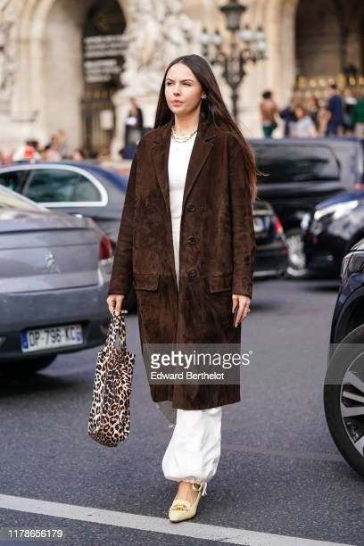 A guest wears necklaces a white top white baggy pants a brown suede coat a leopard print fabric bag beige shoes outside Stella McCartney during Paris...