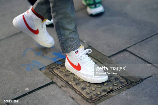 Guest wears Nike sneakers shoes, during London Fashion Week February 2020 on February 17, 2020 in London, England.