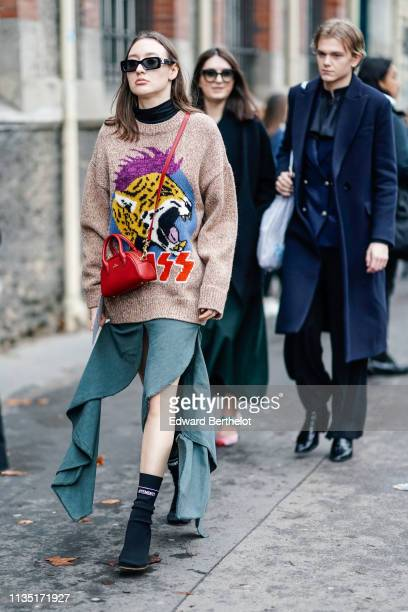 A guest wears OffWhite sunglasses a black top a light brown knit sweater with a leopard head design a red Uooyaa bag a green ruffled split skirt...