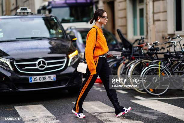 A guest wears OffWhite sunglasses earrings a necklace an orange sweater black sport pants with orange stripes on the side a black and white bag white...