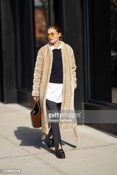 Guest wears orange glasses, a fluffy coat, a white shirt, a dark blue pullover, gray slit pants, black leather shoes, a brown leather bag, outside...
