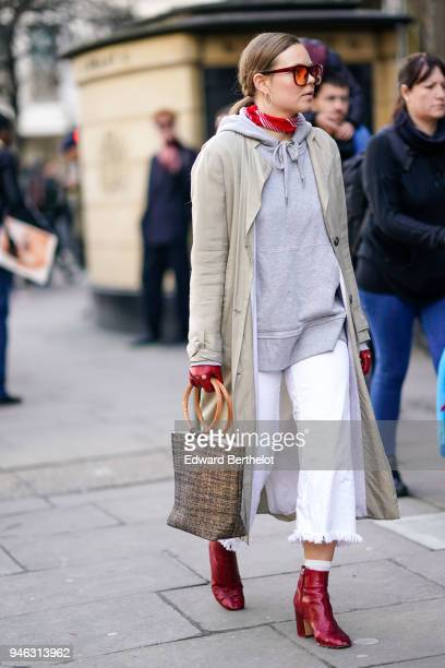 A guest wears orange glasses a gray hoodie sweater a trench coat red gloves a bag red leather shoes during London Fashion Week February 2018 on...