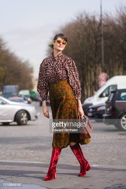 Guest wears orange sunglasses, a leopard print shirt, a skirt, a bag, red velvet boots, outside Chanel, during Paris Fashion Week - Womenswear...