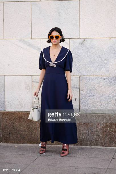 Guest wears orange sunglasses, a navy blue low-neck v-neck dress, a white bag, shoes, outside Vivetta, during Milan Fashion Week Fall/Winter...