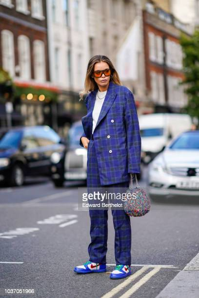 A guest wears orange transparent sunglasses a blue tartan checked pattern blazer jacket a white top a necklace flared pants Nike blue sneakers shoes...