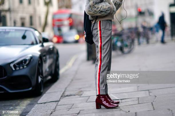 A guest wears pants with red stripes leather shoes during London Fashion Week Men's January 2018 at on January 6 2018 in London England