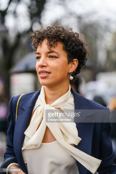 Guest wears pearl earrings, a blue jacket, a white silky scarf, a white top with keyhole, outside Chloe, during Paris Fashion Week - Womenswear...
