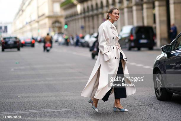 Guest wears pearl earrings, a cream-color double-breasted coat, black wide-legs crop pants, Chanel blue-grey and white slingback pumps , outside...