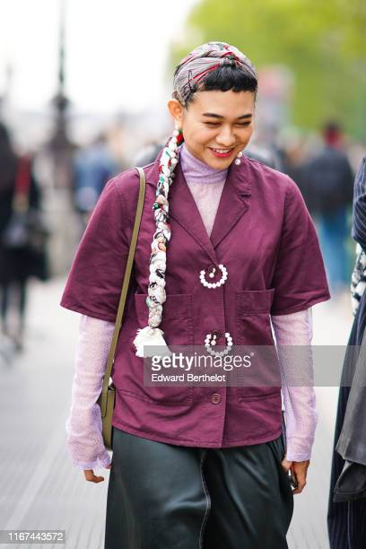 A guest wears pearl earrings a headscarf with a colorful fabric braid a mauve hineck tulle top with glittering tiny silver dots a plumcolor short...