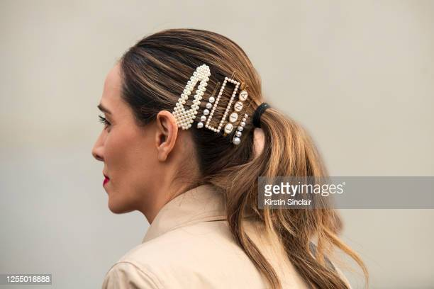 Guest wears pearl hair slides and clips on March 03, 2020 in Paris, France.