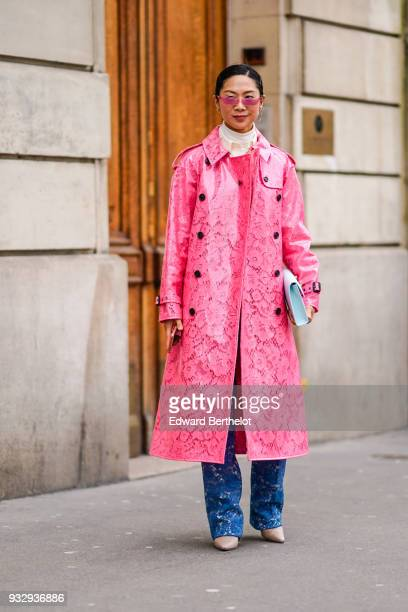 A guest wears pink glasses a patterned pink vinyl trenchcoat a white clutch patterned blue jeans beige pointy toe shoes during Paris Fashion Week...