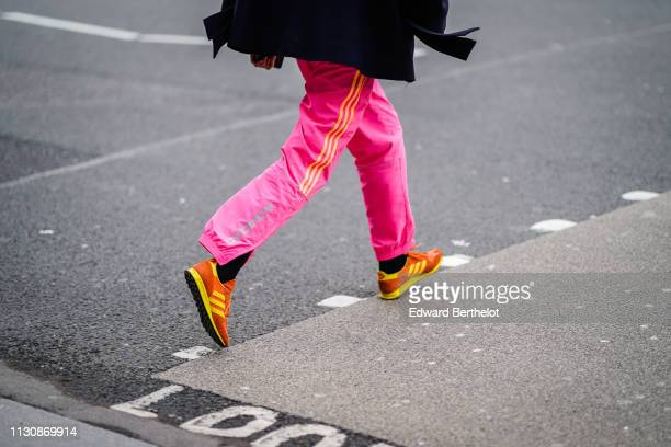 A guest wears pink sport pants from Adidas with yellow stripes on the side orange and yellow AdidasTrx runner sneakers during London Fashion Week...