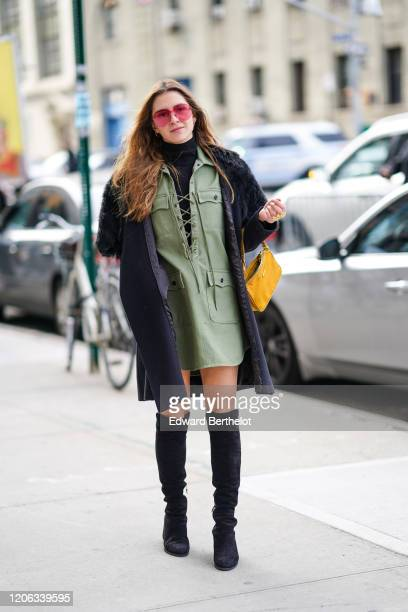 A guest wears pink sunglasses a green khaki dress a navy blue long coat with fluffy parts a yellow bag black suede thigh high boots during New York...