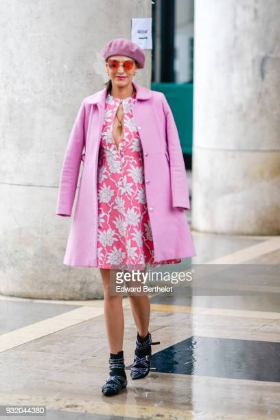 A guest wears pink sunglasses a pink beanie a pink coat a pink and white floral print dress black and white strappy pointy toe shoes during Paris...