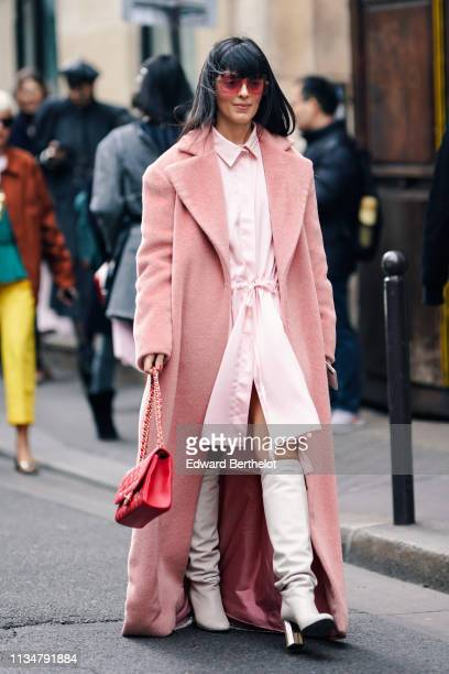 A guest wears pink sunglasses an oversize pink fluffy coat a pale pink shirtdress with a sliding belt white boots with shiny silver heels a red...