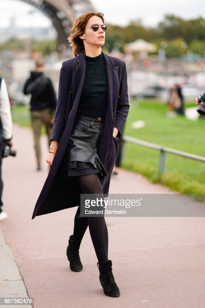 A guest wears purple coat a green top pull over a leather skirt tights black suede shoes outside Hermes during Paris Fashion Week Womenswear...