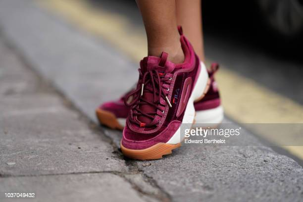 A guest wears purple Fila sneakers shoes during London Fashion Week September 2018 on September 14 2018 in London England