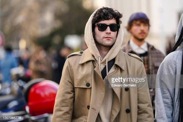 Guest wears Ray Ban sunglasses, a beige hooded sweatshirt, a sand-color trench coat, outside Wooyoungmi, during Paris Fashion Week - Menswear F/W...