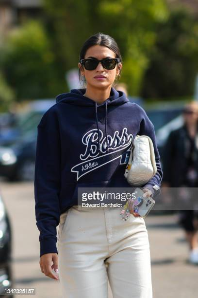Guest wears Ray Ban sunglasses, gold earrings, a navy blue sweater with Boss embroidered logo from Boss, white leather handbag form Dior, white...