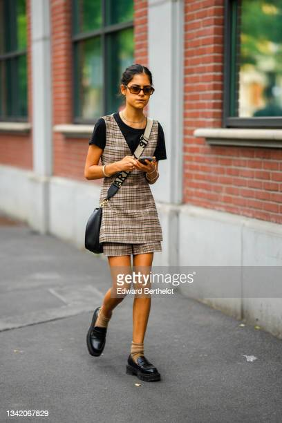Guest wears Ray Ban sunglasses, silver earrings, necklaces, a black t-shirt, a black / brown / beige / pale pink checkered print pattern V-neck long...
