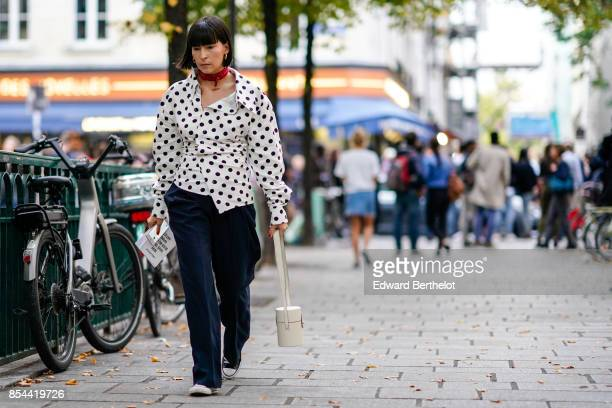 A guest wears red bandanna a shirt with black dots black pants outside Koche during Paris Fashion Week Womenswear Spring/Summer 2018 on September 26...
