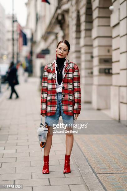 A guest wears red earrings a black turtleneck a white shirt a red tartan oversize jacket denim shorts a semitransparent bag with a rainbow color...
