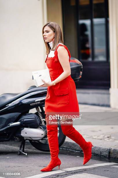 Guest wears red earrings, a white turtleneck, a scalloped hem red dress, red suede pointy kitten-heeled thigh high boots, outside Elie Saab, during...