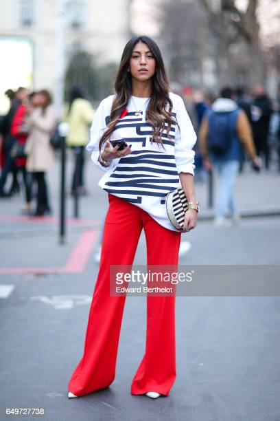 A guest wears red flared pants and a white sweater with a printed inscription outside the Andrew GN show during Paris Fashion Week Womenswear...