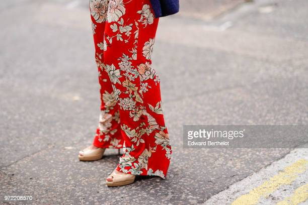 A guest wears red flower print flared pants during London Fashion Week Men's June 2018 on June 09 2018 in London England