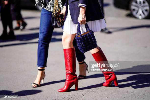 A guest wears red leather boots and a blue dior bag outside Ann Demeulemeester during Paris Fashion Week Womenswear Spring/Summer 2019 on September...