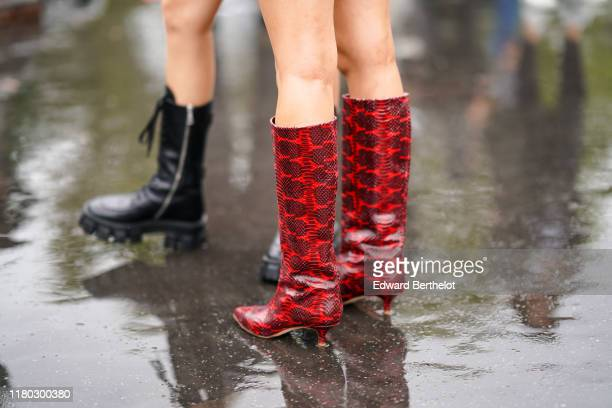 Guest wears red leather snake print boots, outside Chanel, during Paris Fashion Week - Womenswear Spring Summer 2020, on October 01, 2019 in Paris,...