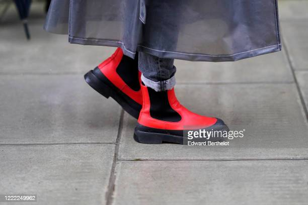Guest wears red rubber shoes, during London Fashion Week Fall Winter 2020 on February 16, 2020 in London, England.