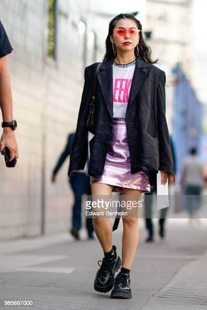 A guest wears red sunglasses a black blazer jacket a white tshirt with pink prints a pink glitter skirt black leather shoes outside 1017 ALYX 9SM...