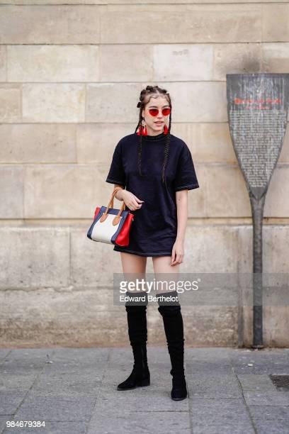 A guest wears red sunglasses a black dress a bag high boots outside Christian Dada during Paris Fashion Week Menswear SpringSummer 2019 on June 24...