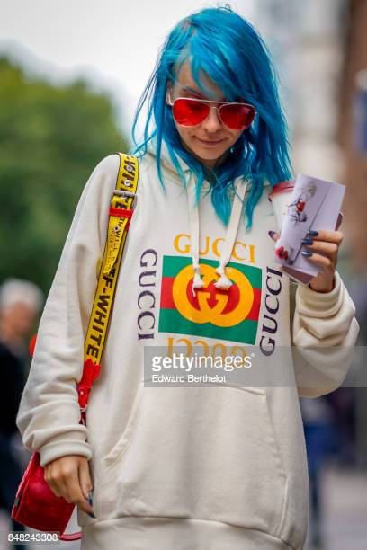 A guest wears red sunglasses a Gucci hoodie an Off White bag and has blue hair outside Fashion East during London Fashion Week September 2017 on...