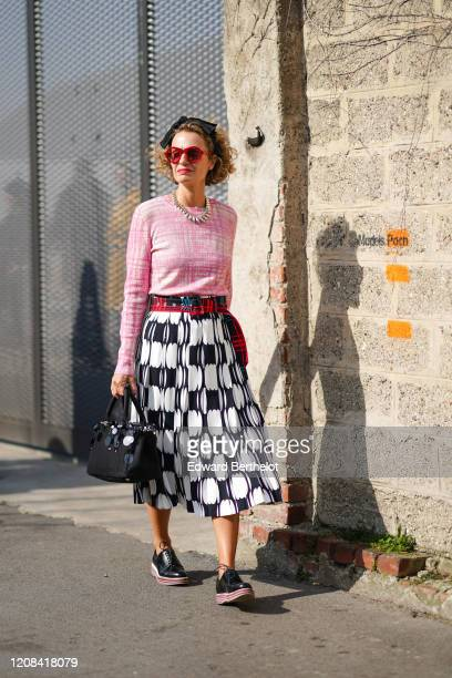 Guest wears red sunglasses, a metallic silver necklace, a pink pullover, a black and white skirt, a black bag, black leather shoes, a headband,...