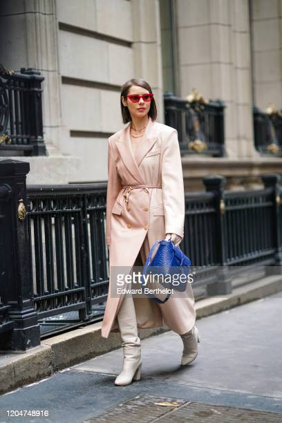 Guest wears red sunglasses, a pale pink long trench coat, a blue crocodile pattern leather bag, gray boots, golden necklace, outside Cinq a Sept,...