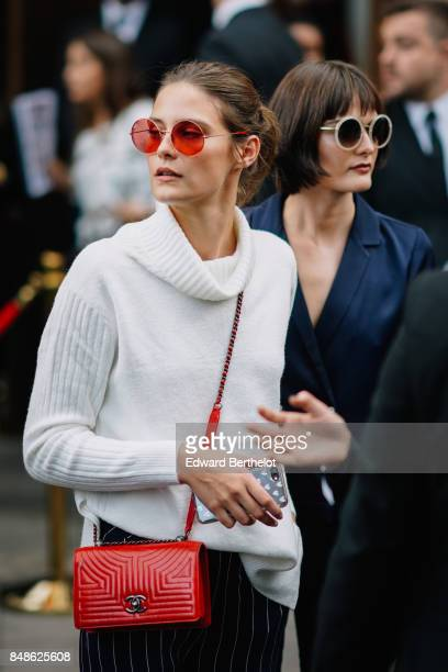 A guest wears red sunglasses a white turtleneck pull over a Chanel red bag outside Topshop during London Fashion Week September 2017 on September 17...