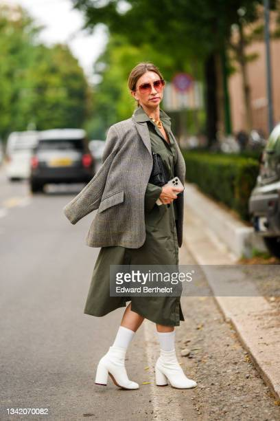 Guest wears red sunglasses, silver earrings, a large gold chain necklace, a khaki oversized long shirt dress, a gray and white print pattern...