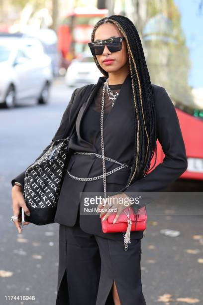 A guest wears red trainers with a red handbag outside BFC show space during London Fashion Week September 2019 on September 13 2019 in London England