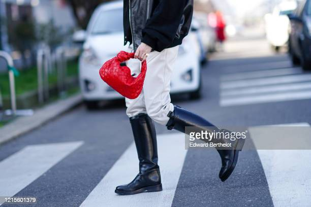 A guest wears rings a black leather jacket with black suede sleeves white leather pants black riding boots a red woven leather handbag outside MSGM...