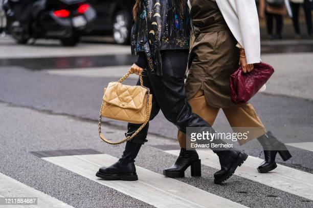 Guest wears rings, a black leather jacket with colorful moons and stars print, black leather pants with rolled-up hem, black boots, a sand-color...